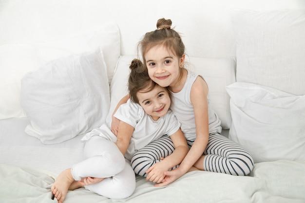 Duas garotas lindas irmãzinhas estão abraçando na cama no quarto.