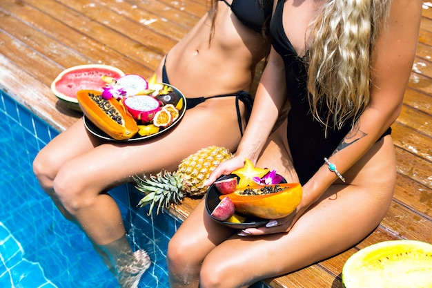 Duas garotas lindas loiras e morenas se divertindo e enlouquecendo na festa de frutas tropicais, biquíni preto sexy, muita comida vegana doce, férias exóticas, posando perto de piscina, imagem de moda de verão.