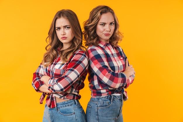 Duas garotas lindas vestindo camisa xadrez franzindo a testa e isoladas costas com costas