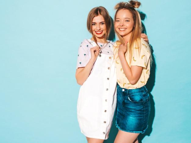 Duas garotas loiras hipster sorrindo lindas jovens em roupas de camiseta colorida na moda verão. e abraçando