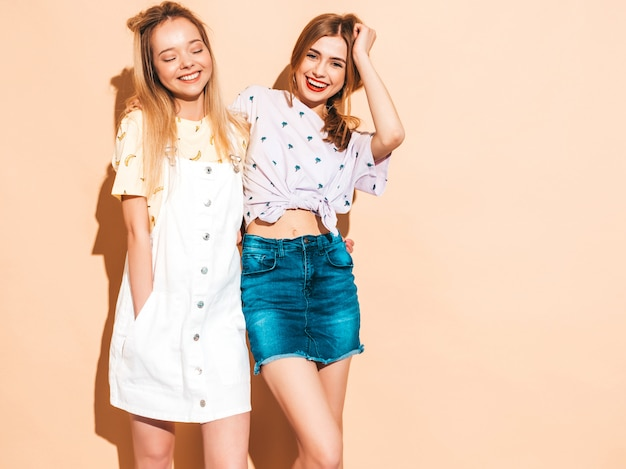 Duas garotas loiras hipster sorrindo lindas jovens em roupas de camiseta colorida na moda verão.
