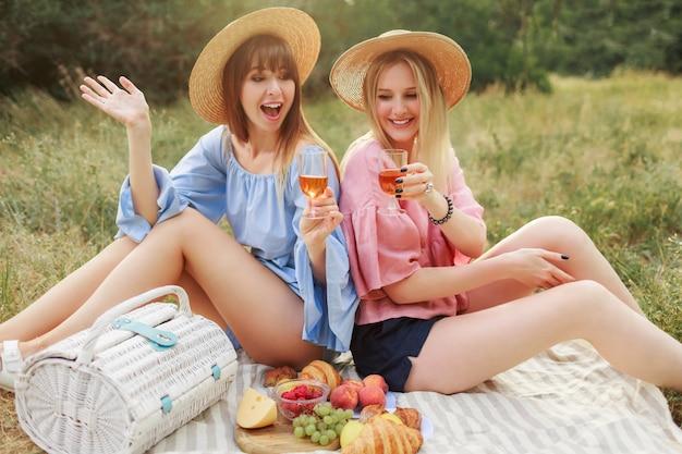Duas garotas maravilhosas com chapéu de palha, passar as férias no campo, bebendo vinho espumante.