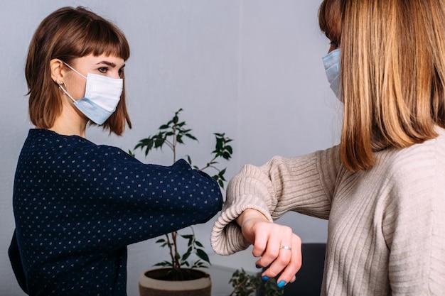 Duas garotas mascaradas no trabalho cumprimentam seus cotovelos. distanciamento social. nova realidade. conceito de vida durante a pandemia do coronavírus.