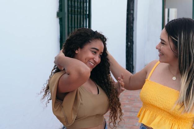 Duas garotas milenares conversam e riem enquanto caminham pela rua.