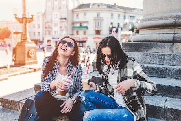 Duas garotas morenas de cabelos longos conversando e bebendo café ao ar livre