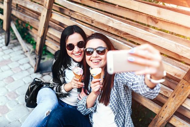 Duas garotas morenas de cabelos longos fazendo selfie ao ar livre