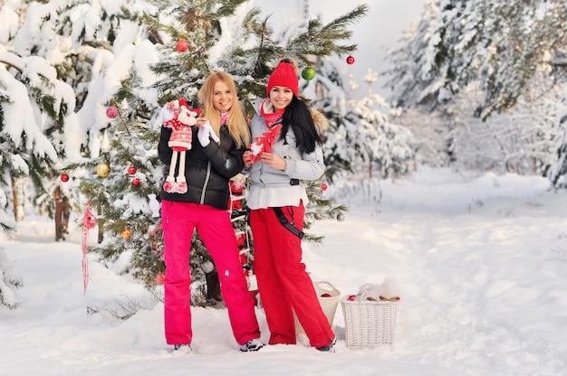 Duas garotas na floresta de inverno perto de uma árvore de natal decorada. garotas em uma árvore de natal em uma floresta de neve