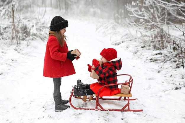 Duas garotas na floresta em um dia gelado de inverno trocam presentes de natal