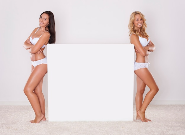 Duas garotas naturais posando ao lado do quadro branco