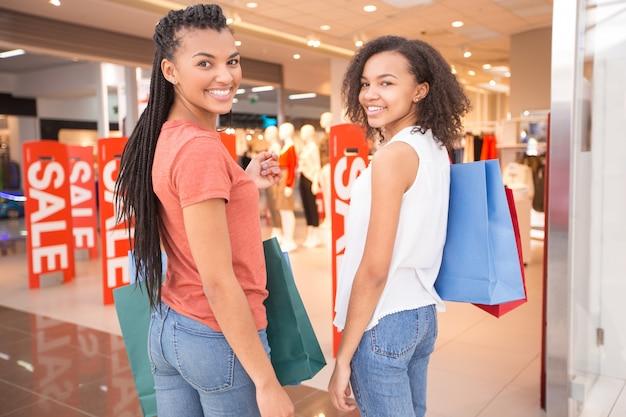 Duas garotas negras felizes shopping e turning round