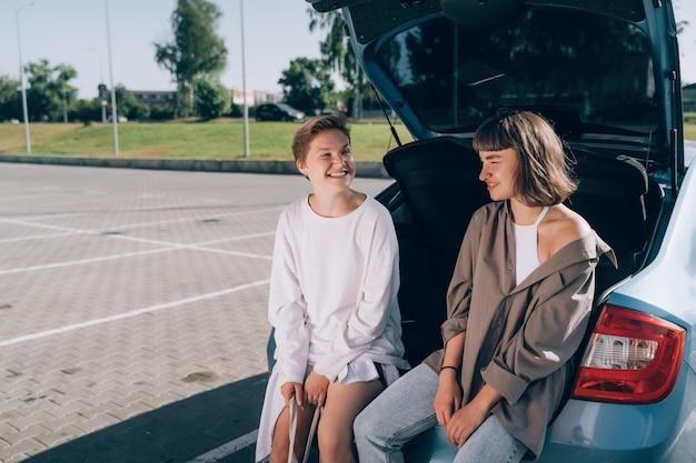 Duas garotas no estacionamento no porta-malas aberto posando para a câmera.