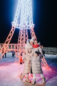 Duas garotas no inverno com as luzes da véspera de ano novo acesas na rua de natal
