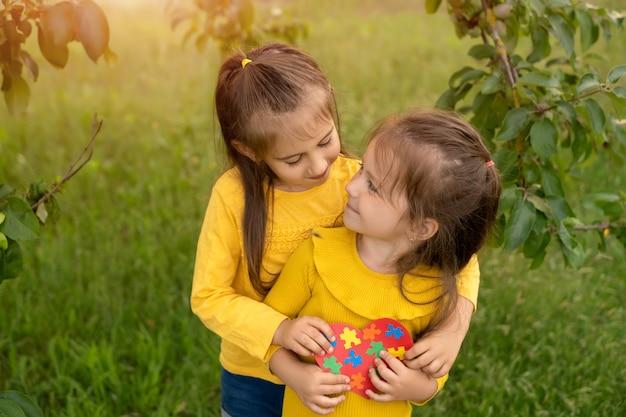 Duas garotas no parque se abraçando segurando um coração feito de quebra-cabeças