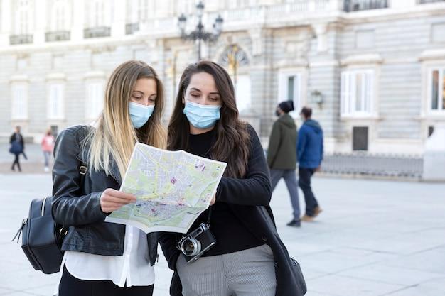 Duas garotas olhando para um mapa turístico na rua. eles estão usando máscaras faciais. conceito de viagem durante a pandemia de covid-19.