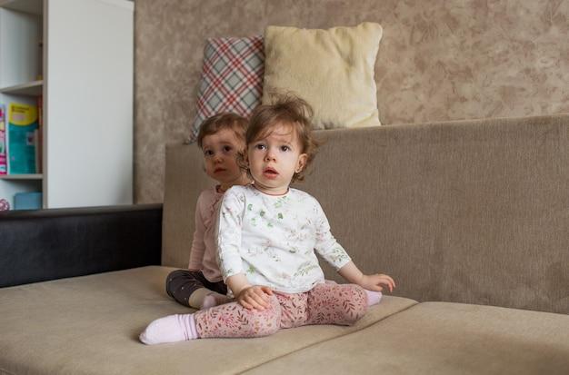 Duas garotas pequenas semelhantes estão sentadas no sofá