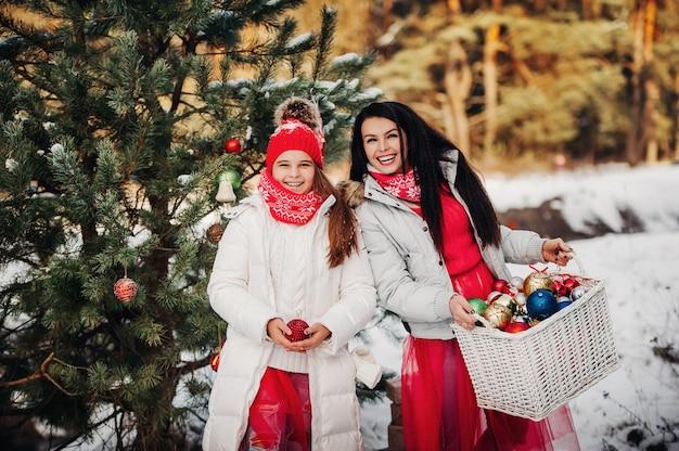 Duas garotas perto da árvore de natal com presentes. decoração da árvore de natal na rua no inverno. muitas bolas de natal na árvore de natal.