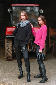 Duas garotas posando ao lado de um trator