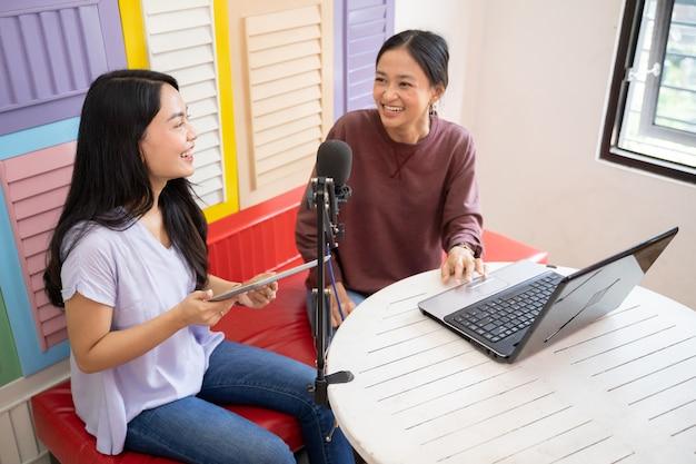 Duas garotas rindo enquanto conversam em um podcast usando um laptop