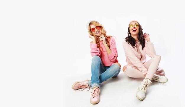 Duas garotas rindo, melhores amigas, posando no estúdio em fundo branco. roupa de inverno rosa na moda.