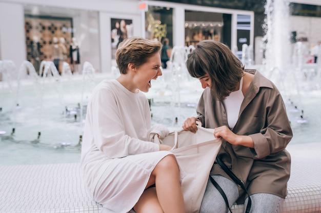 Duas garotas se divertem no shopping, ao lado de uma fonte