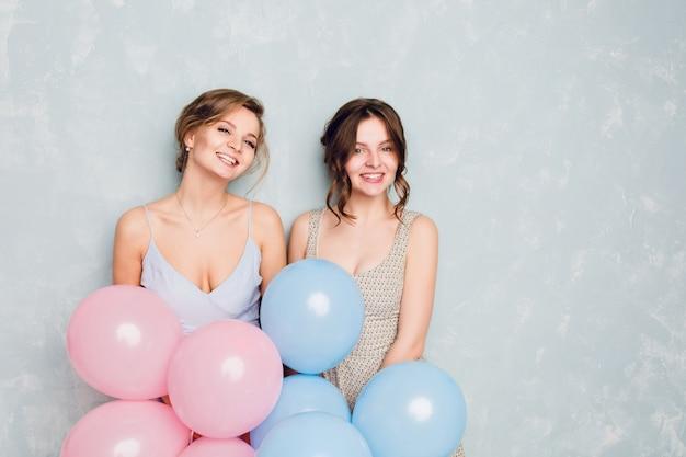 Duas garotas se divertindo em um estúdio e brincando com balões azuis e rosa.