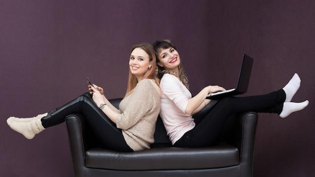 Duas garotas se sentam no sofá, de costas uma para a outra.