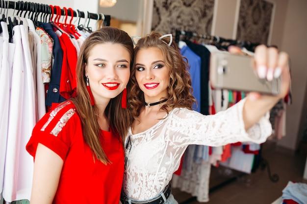 Duas garotas segurando o smartphone e tendo o auto-retrato na loja.