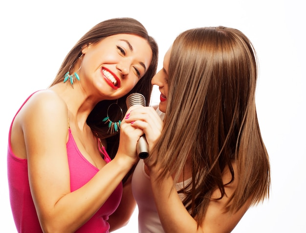 Duas garotas sensuais cantando com microfone, isolado no branco