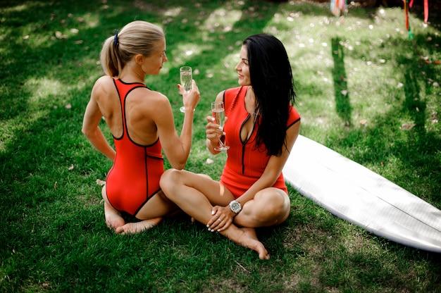 Duas garotas sentadas e bebem champanhe perto do wakeboard