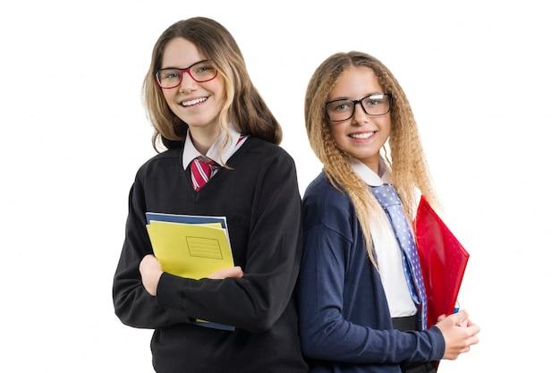 Duas garotas sorridentes do ensino médio de uniforme usando óculos