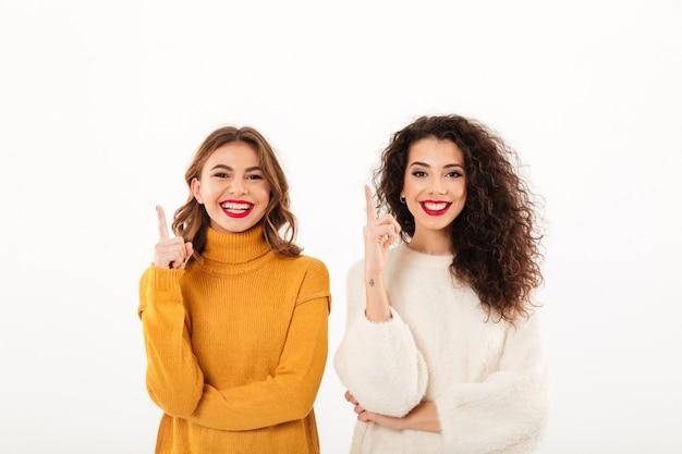 Duas garotas sorridentes em blusas apontando para cima sobre parede branca