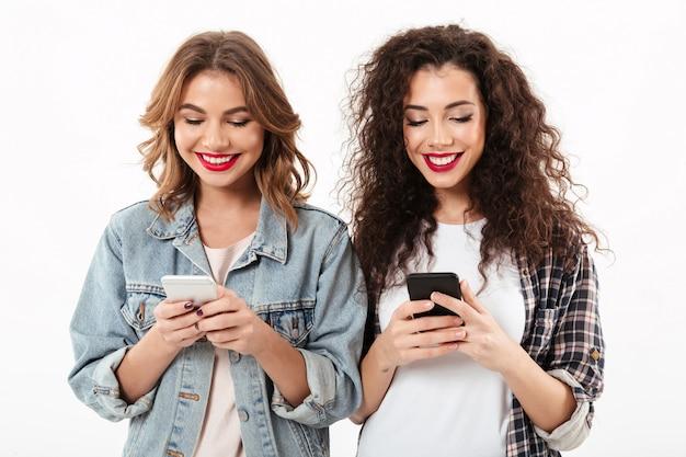 Duas garotas sorridentes, escrevendo a mensagem no smartphone ther sobre parede branca