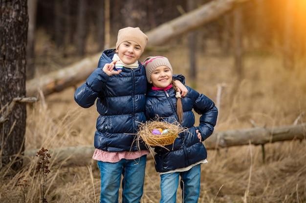 Duas garotas sorridentes posando com uma cesta cheia de ovos de páscoa na floresta