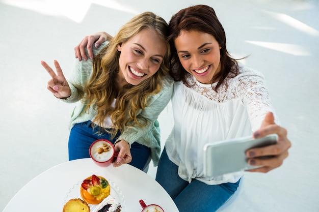 Duas garotas tiram uma selfie enquanto comem e bebem café
