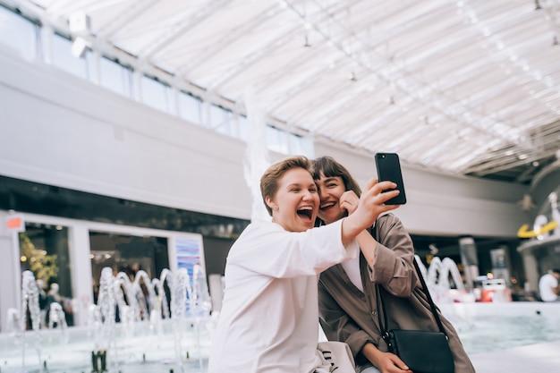 Duas garotas tiram uma selfie no shopping, ao lado de uma fonte