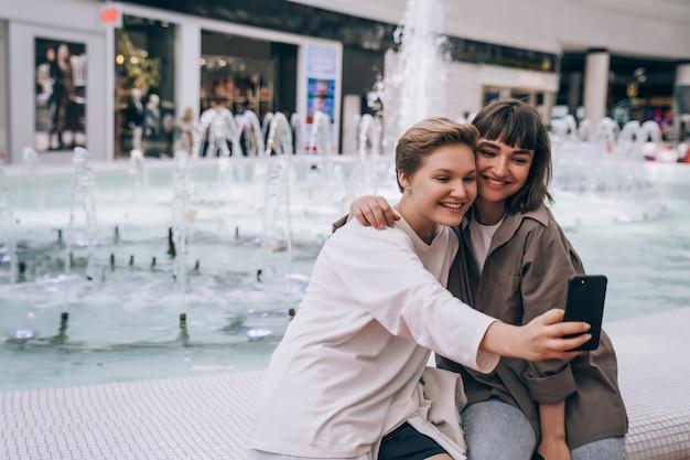 Duas garotas tiram uma selfie no shopping, uma fonte no fundo