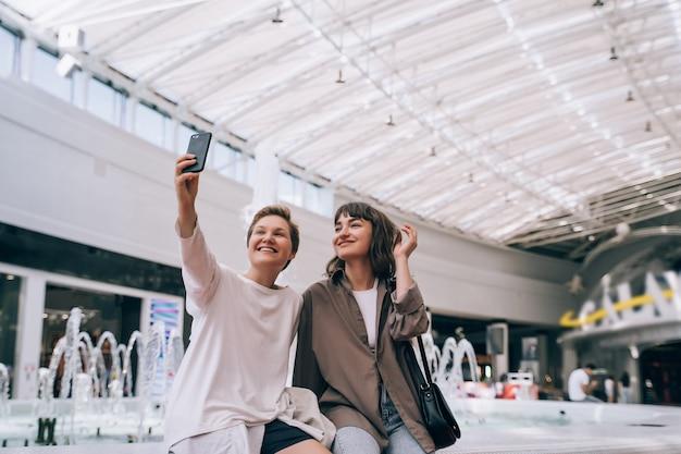 Duas garotas tiram uma selfie no shopping, uma fonte