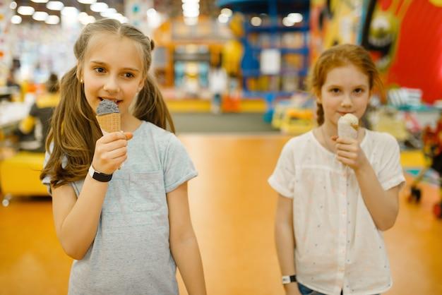 Duas garotas tomam sorvete no centro de entretenimento. lazer infantis nos feriados, felicidade infantil, crianças felizes no parquinho