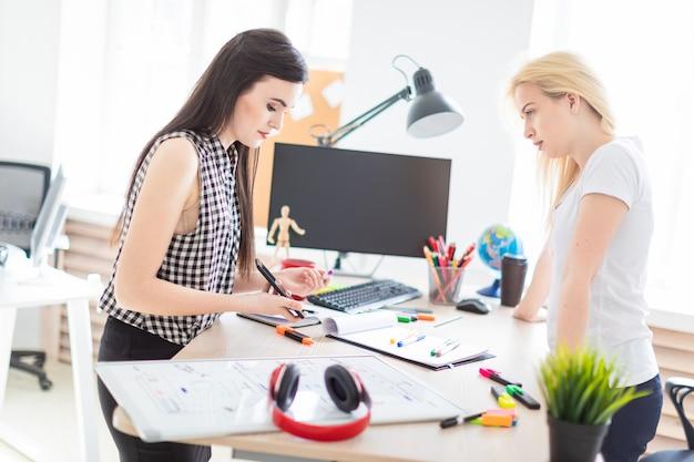 Duas garotas trabalham no escritório. menina segurando um telefone.