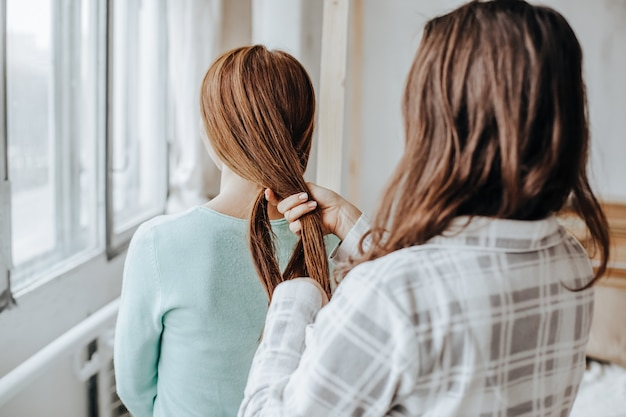 Duas garotas trançam os cabelos na janela. mulher faz uma trança para a amiga. penteados de tecelagem de cabelo. namorada trança as mãos com cachos. cuidado capilar