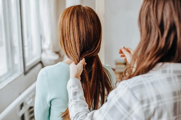 Duas garotas trançam os cabelos na janela. mulher fazendo uma trança para a amiga