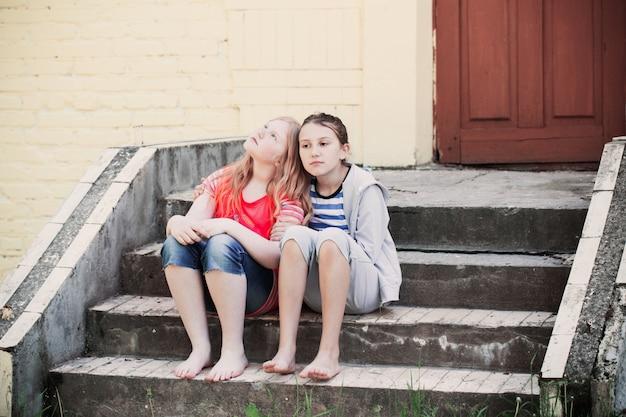 Duas garotas tristes na parede do fundo
