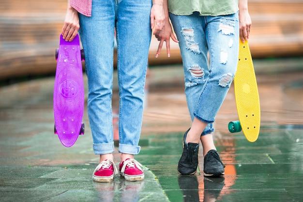 Duas garotas urbanas hipster com skate ao ar livre na luz do sol
