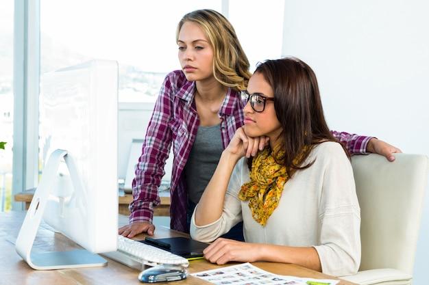 Duas garotas usam um computador em um escritório