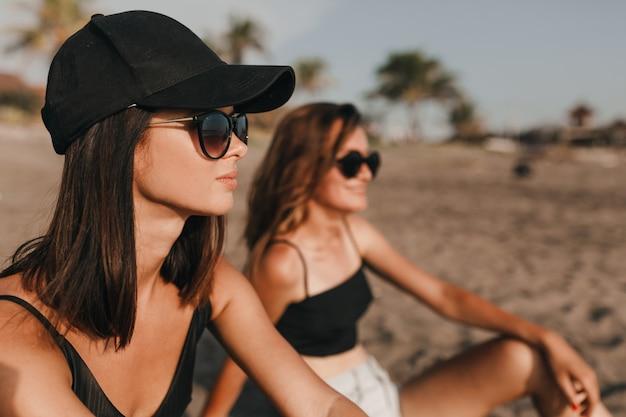 Duas garotas usando óculos escuros e maiôs sentadas na praia com palmeiras e olhando para o mar com sorrisos românticos duas melhores amigas passam as férias nos trópicos