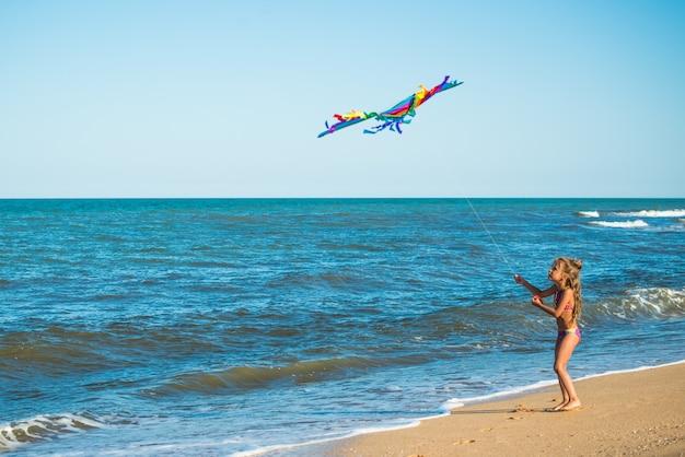 Duas garotinhas alegres e felizes correndo com uma pipa na praia arenosa à beira-mar