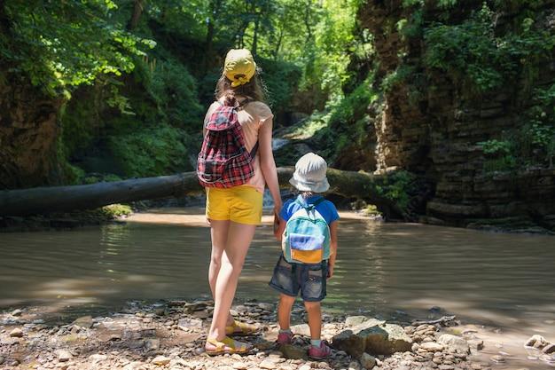 Duas garotinhas com uma mochila em uma caminhada nas montanhas nas cachoeiras