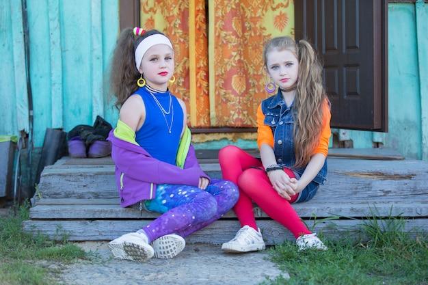 Duas garotinhas engraçadas com maquiagem brilhante vestidas no estilo dos anos noventa