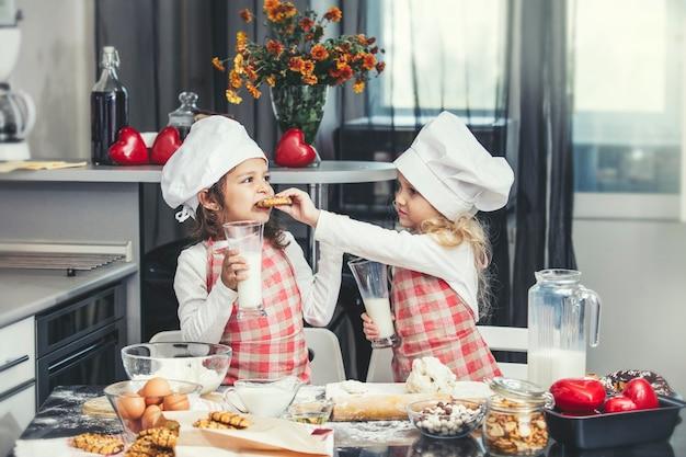 Duas garotinhas felizes bebendo leite e cozinhando na mesa da cozinha é linda e linda