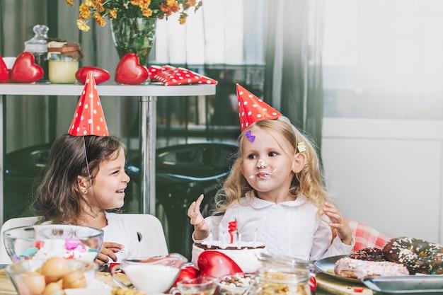 Duas garotinhas felizes comemorando um aniversário com um bolo na mesa é lindo e lindo